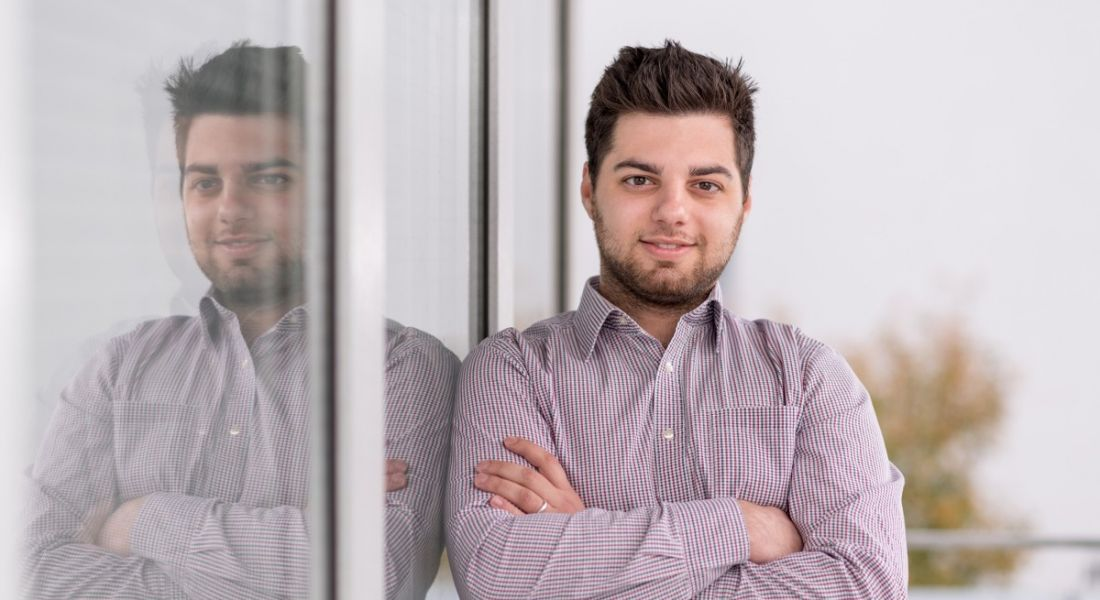 Artur Kane, head of product marketing at Flowmon Networks and NetSecOps expert, is standing against a window showing his reflection with his arms crossed while smiling into the camera.