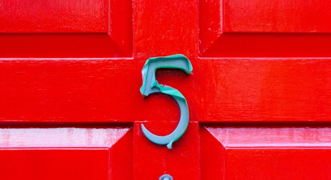 A blue number five on a bright red door.