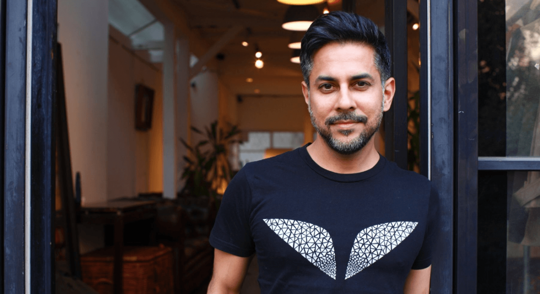 Vishen Lakhiani of Mindvalley is standing in the doorway of a dimly lit room and smiling into the camera.