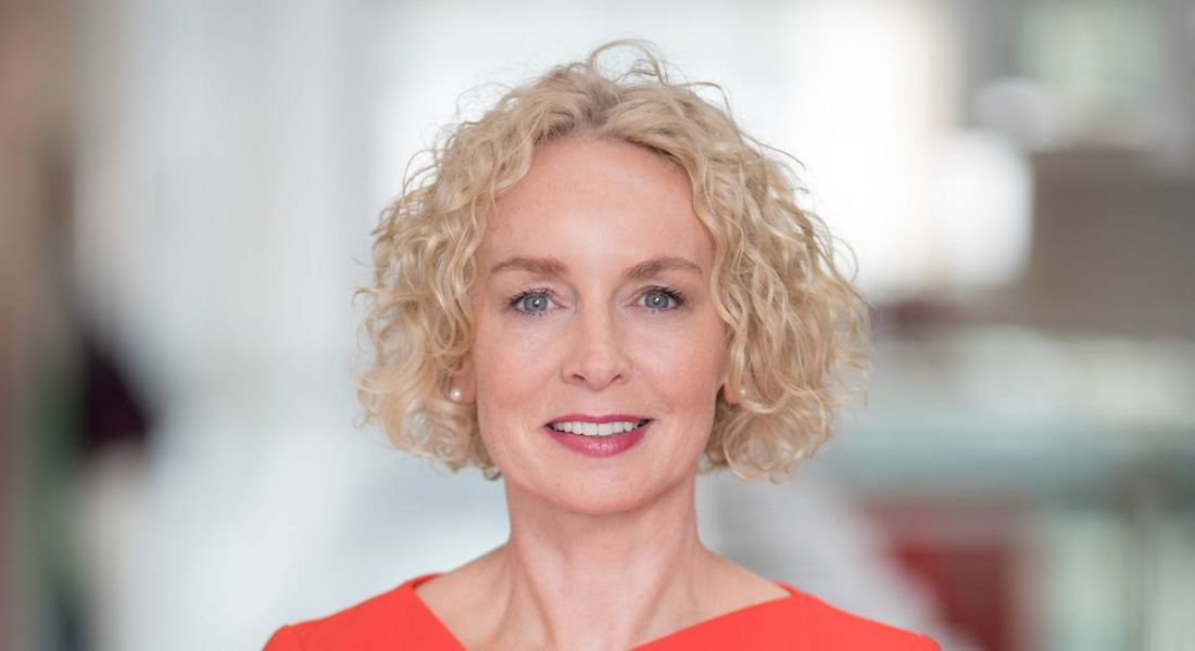 Anne O'Leary of Vodafone is smiling into the camera against a blurred background. She is wearing a red dress.