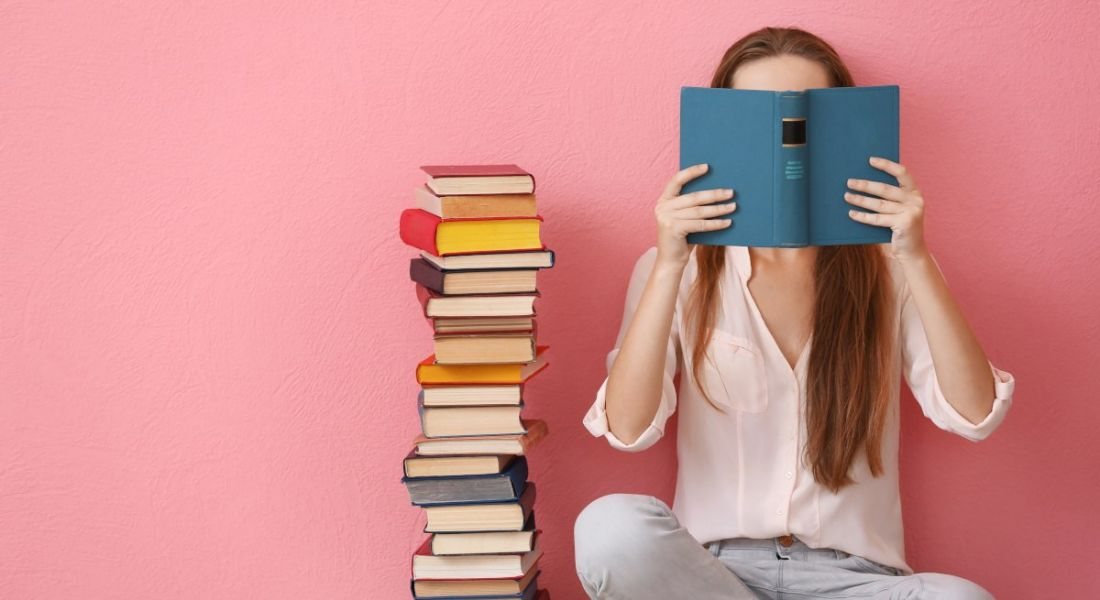 Woman sitting on a floor and reading a book against a pink background, symbolising going back to school during your career.