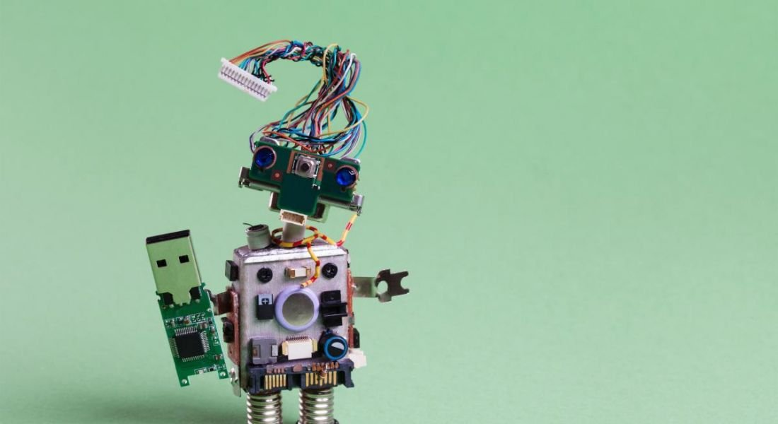 A robot made from electronic components is standing against a light green background.