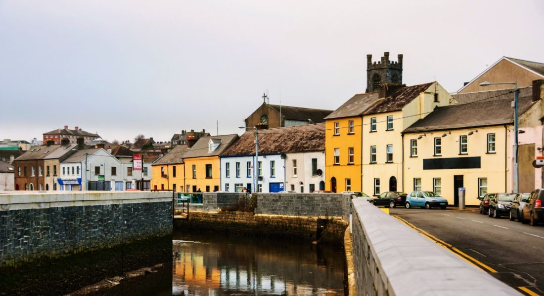 Photo of colourful houses along a river in Co Waterford, Ireland, where StitcherAds is hiring engineers.