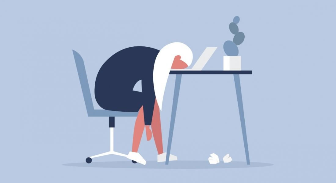 Illustration of a worker who is tired or bored of her job and is resting her head on her desk.