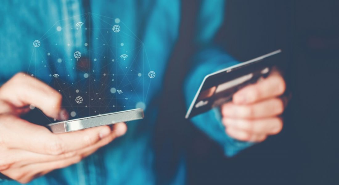 Close-up of a person using a debit card to pay for something on their smartphone.