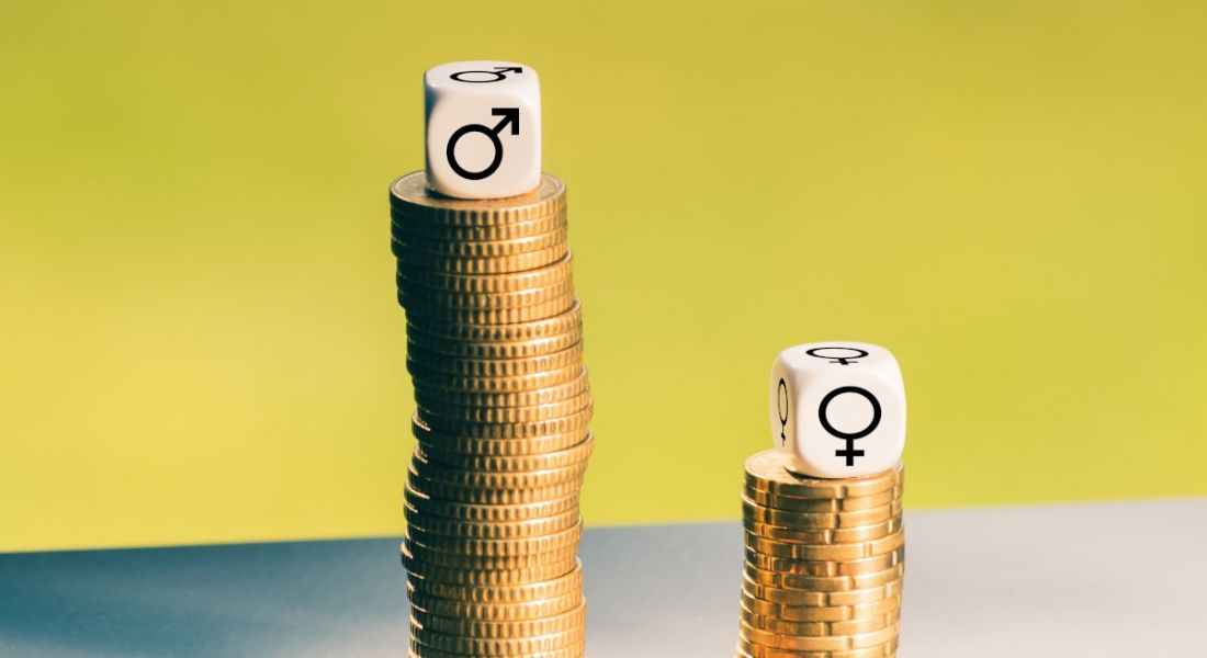 Two stacks of coins, the shorter one has a die with the symbol for women on it and the taller one has the symbol for men on it.