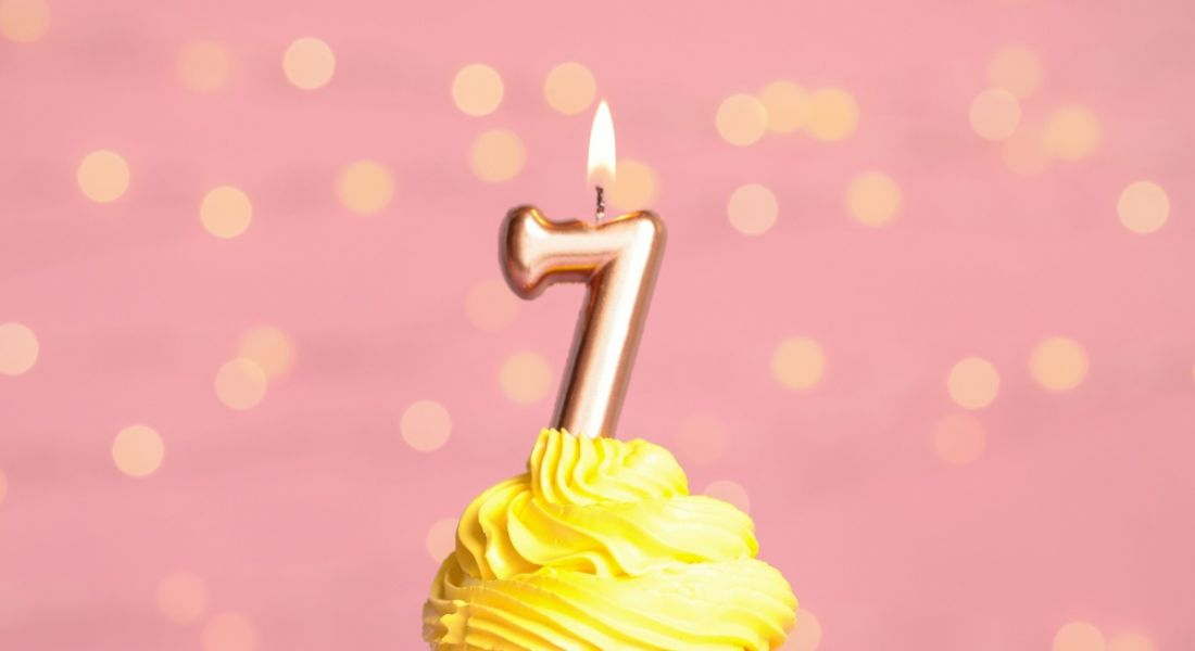 Birthday cupcake with yellow icing and a number seven birthday candle on top, sitting against a pink background.