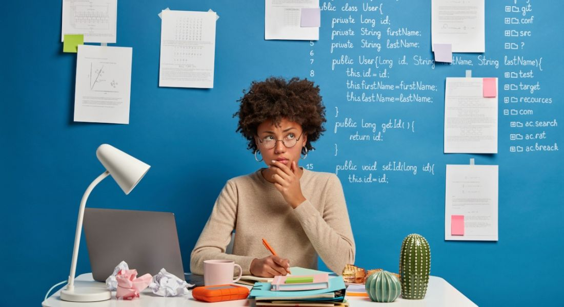 An experienced hire is working on her CV on a laptop in front of a blue wall with multiple pages of ideas stuck to it.