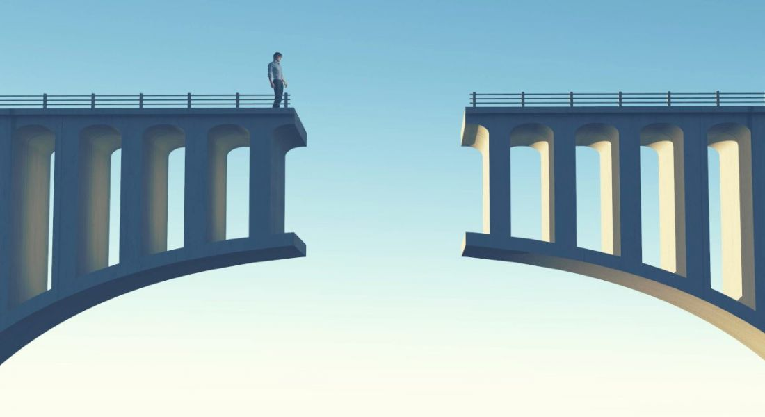 A figure of a person is standing and looking down at a gap in a broken bridge against a blue sky, symbolising a skills gap.