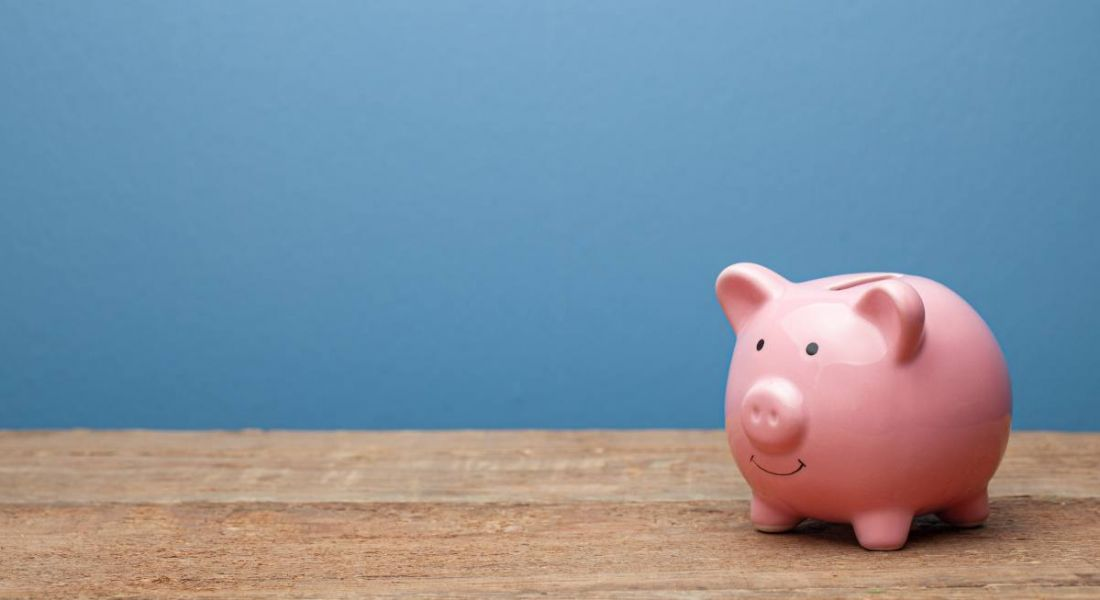 Pink piggy bank on a wooden surface against a blue background.