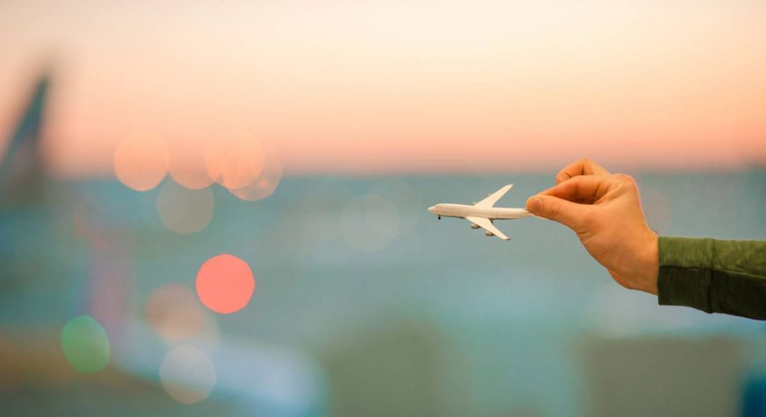 Hands are holding a miniature airplane model up against a blurred background with a sunset.