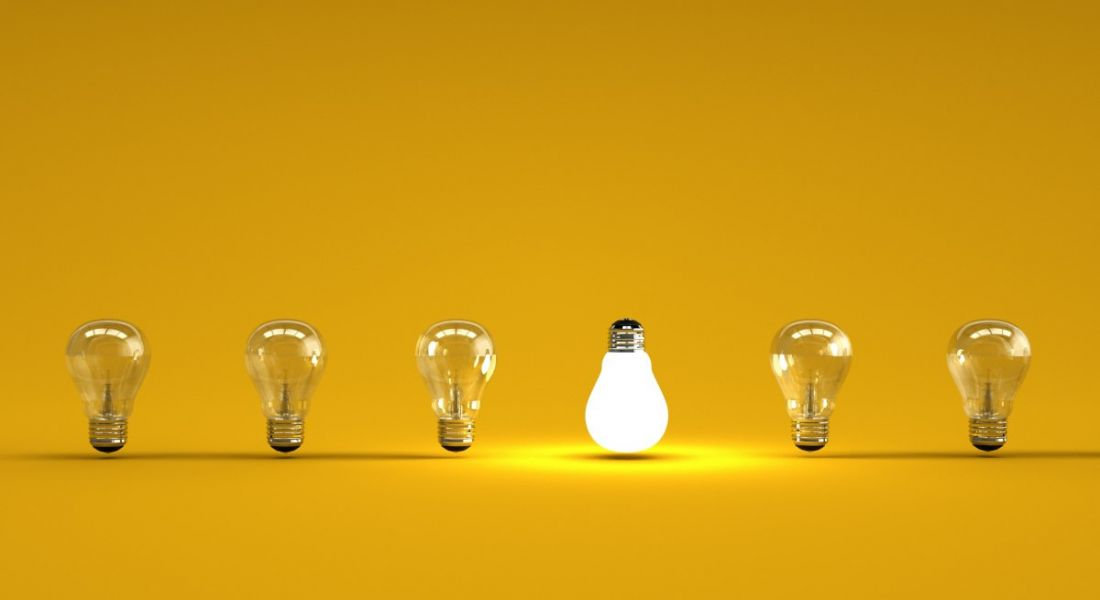 Six lightbulbs are lined up against a yellow background, with one upside down and lit up.