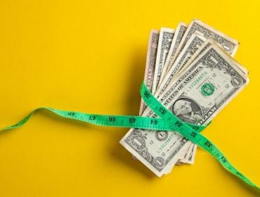 A pile of dollars has a green measuring tape around it on a yellow background.