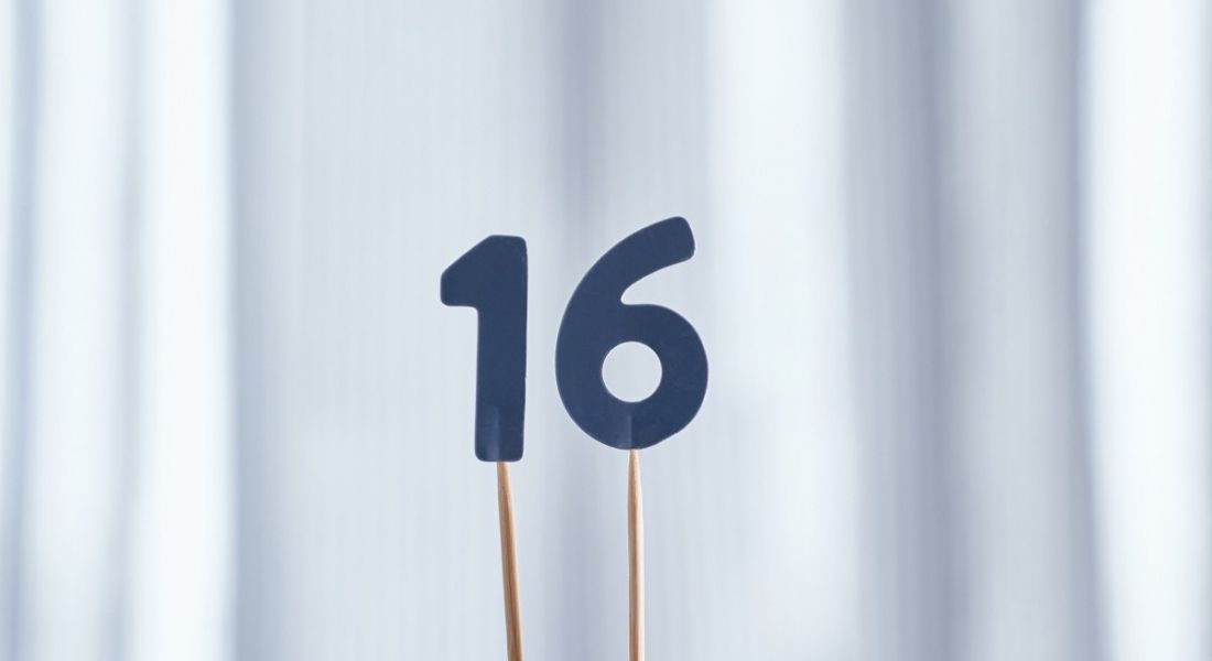 Wooden sticks are holding up the number 16 cut out of blue paper.