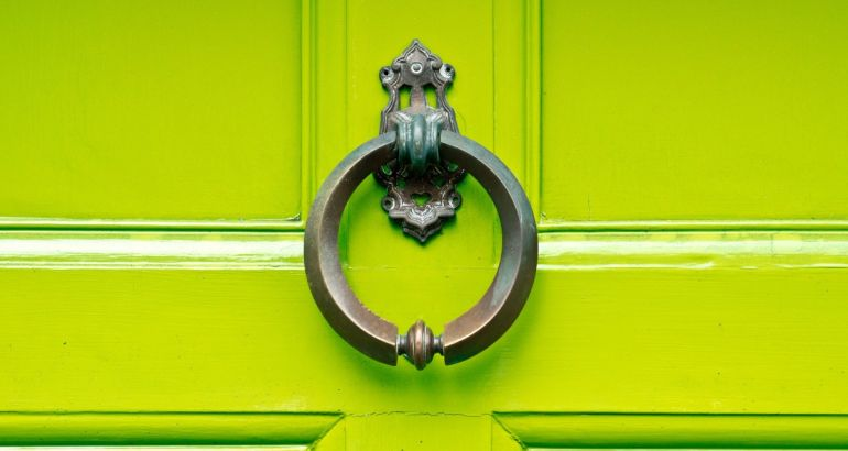 An antique knocker on a lime green wooden door.