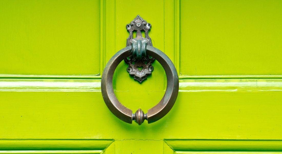 An antique knocker on a lime green wooden door.