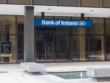 A Bank of Ireland branch in Dublin with the company logo on a blue sign at the top of the doors.