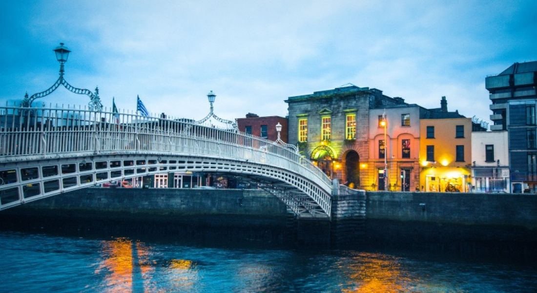 Ha'penny Bridge over the River Liffey in Dublin at dusk. The sky is dark blue and there are lights on buildings in the background.
