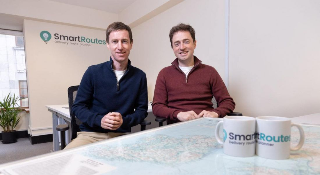Two men are sitting side by side and smiling into the camera with mugs that have SmartRoutes branding.