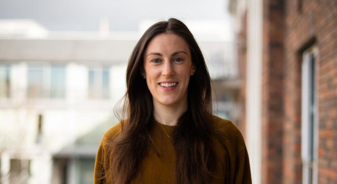 Elaine O'Dwyer, who works at the intersection between data and life sciences, is standing outdoors and wearing a brown jumper while smiling into the camera.