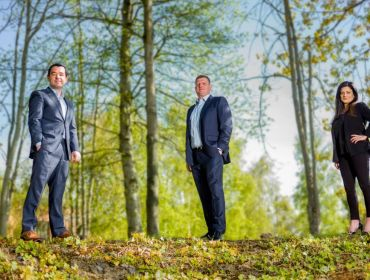 Three people in suits are standing in a wooded area on a bright day for the announcement that Hikari has acquired ProcessUs.