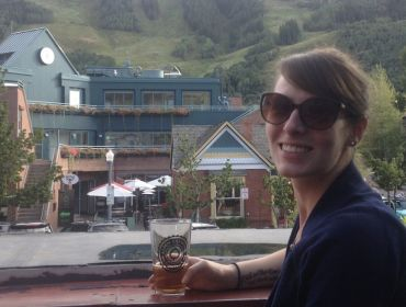 Caitlin Costelle from Genuity Science sits outside a craft brewery enjoying a glass of beer.
