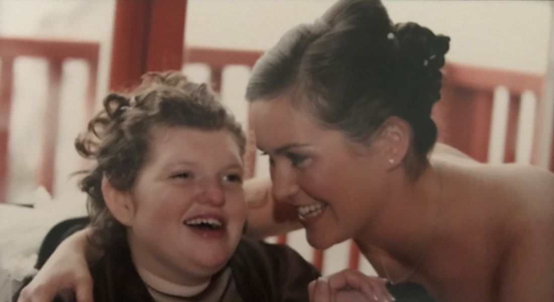 A photograph of Jackie Dolan with her sister laughing together at a family event.
