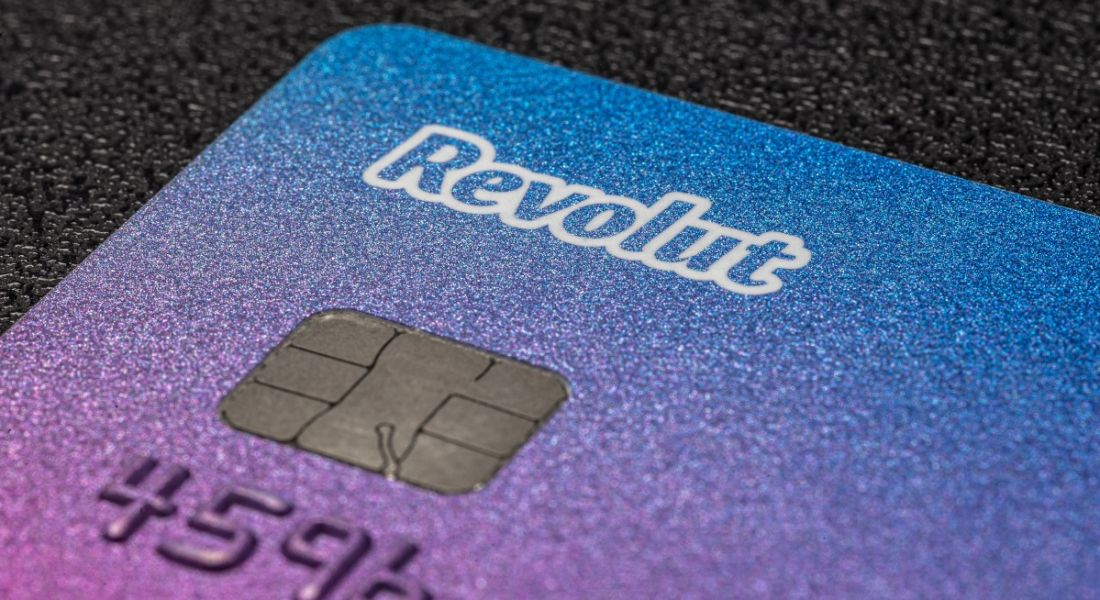 Close-up of a Revolut bank card on a dark surface.