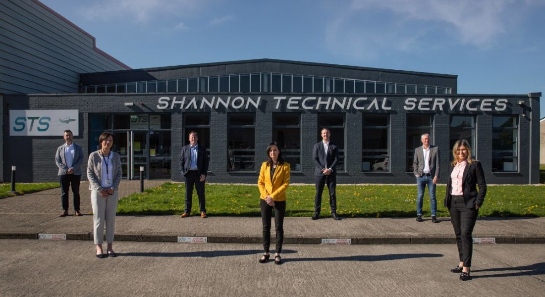 Seven men and women stand a few metres apart outside the Shannon Technical Services building on a sunny day.