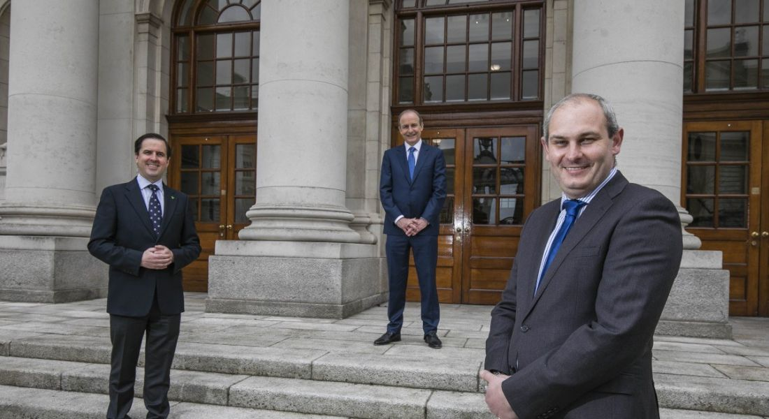 Three men in dark suits stand, socially distanced, on the steps of Government buildings in Dublin.