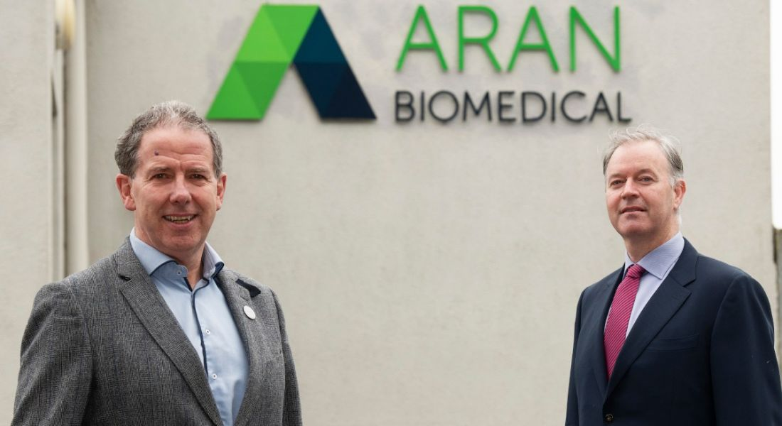 Two men, one in a grey suit and the other in a navy one, stand outside a white building bearing the Aran Biomedical logo.
