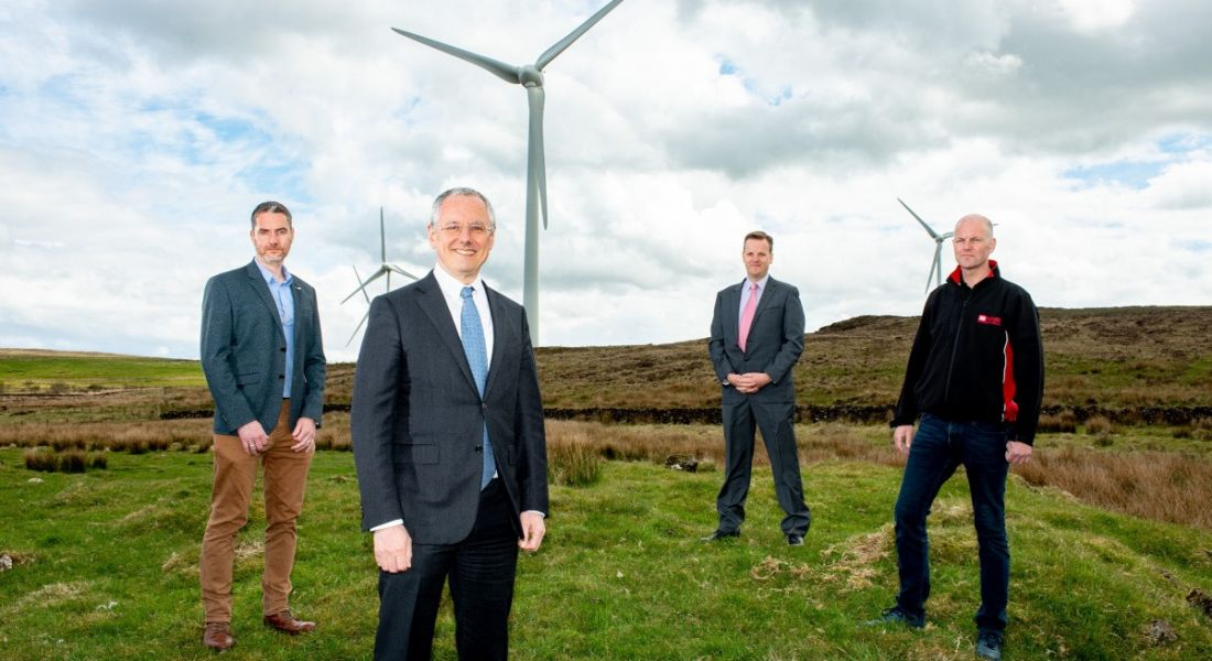Four men in suits are standing outdoors in front of a wind turbine and looking into the camera.
