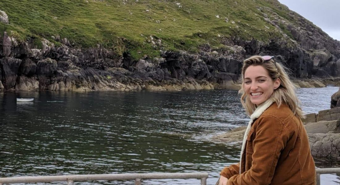 Nicole Moriarty of Patreon is looking back into the camera in an outdoor setting beside a river. She is wearing a brown coat and has blonde hair.