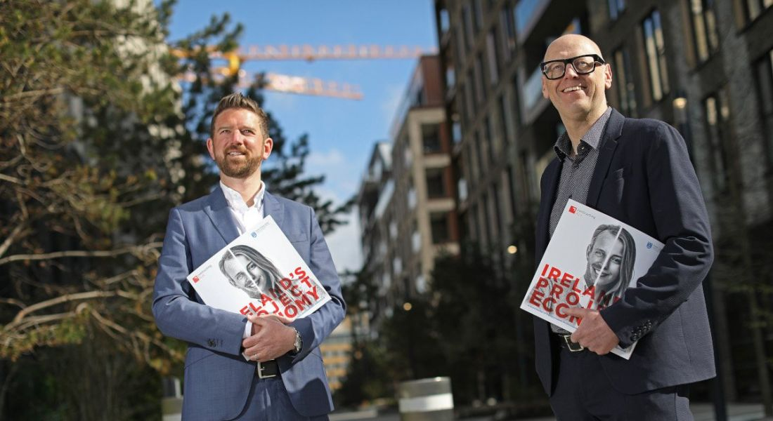 Two men are standing outdoors on a sunny day holding the first edition of an annual report on the project economy in Ireland.