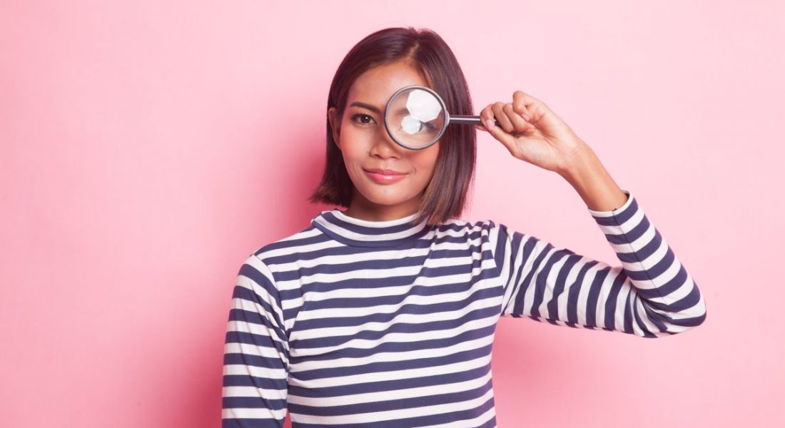 A woman is standing against a pink background wearing a stripey black and white top and looking through a magnifying glass as if she is checking out job opportunities.