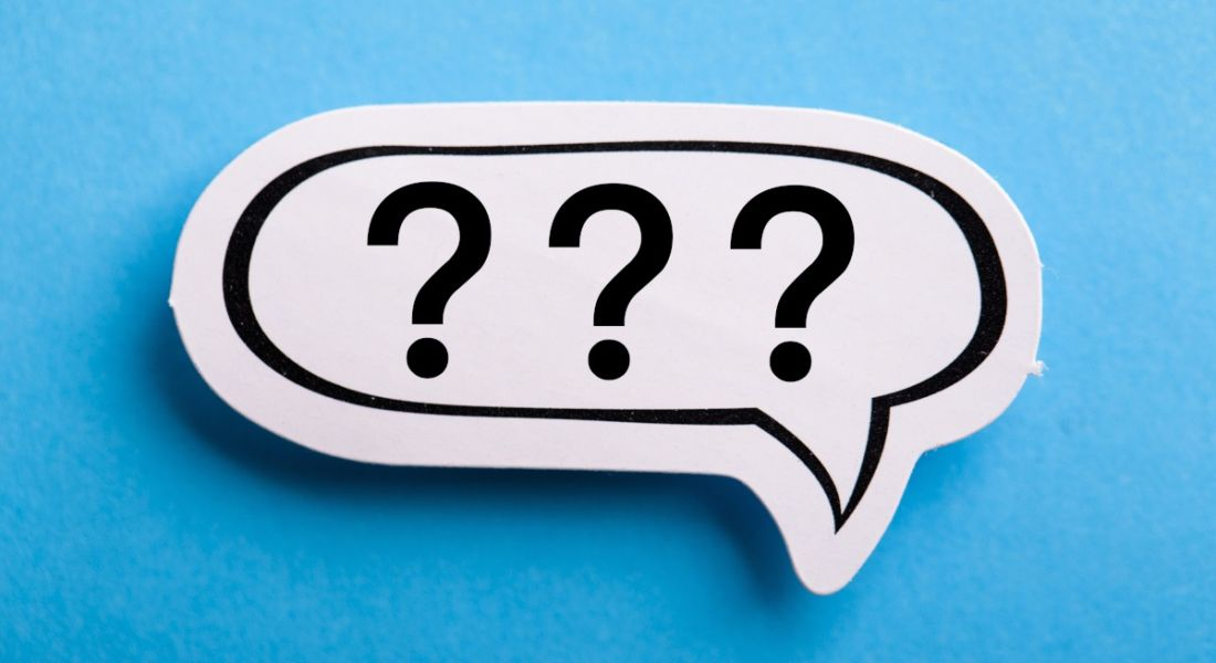 A white speech bubble with three question marks in it is lying against a blue background.