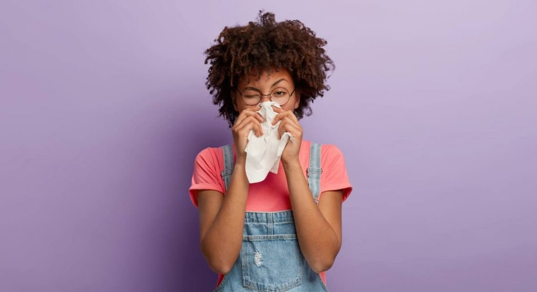 A woman is standing against a purple background wearing dungarees and glasses, sneezing into a tissue.