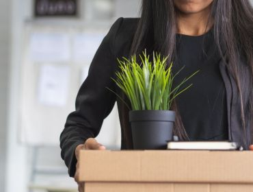 A professional woman is carrying a cardboard box of belongings with a plant on top as she quits her job.