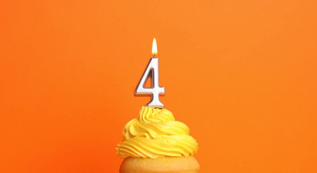 A birthday cupcake with yellow icing and a number four candle is sitting against an orange background.