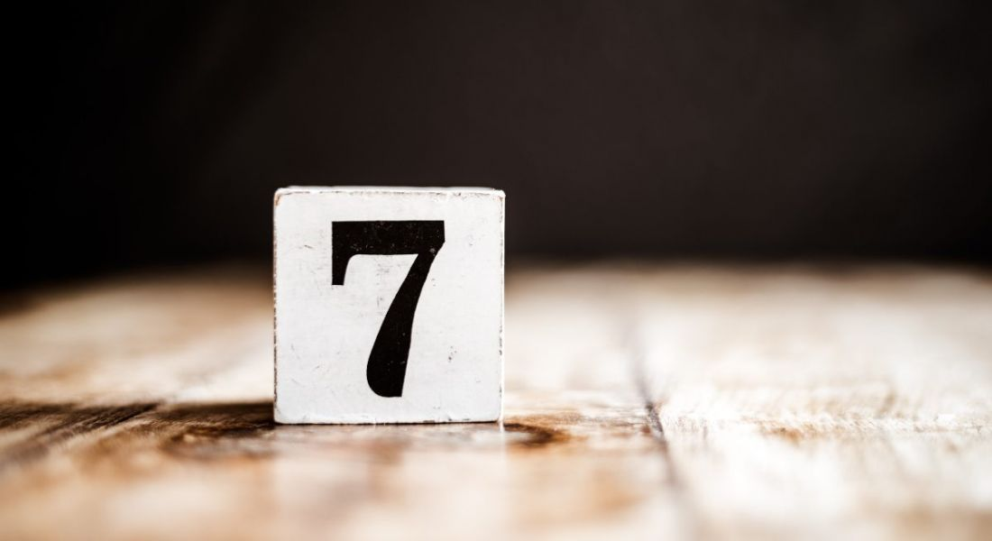 A white block with the number seven on it is sitting on a wooden table.