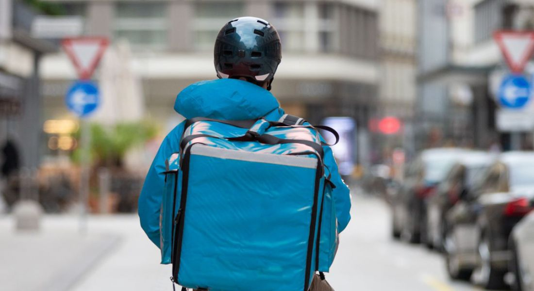 A gig worker is carrying a thermal blue bag on his back, while stopped in the middle of a city street.