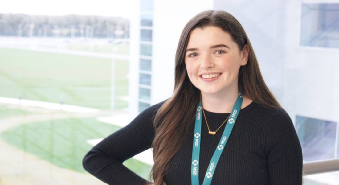 Aoife Dillon of MSD is standing in front of a window and smiling into the camera.