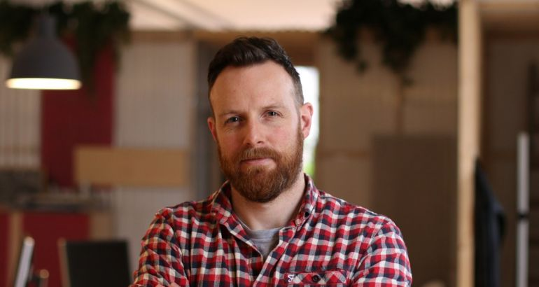 A headshot of Brian Herron, founder and director of Each&Other. He's wearing a check shirt.