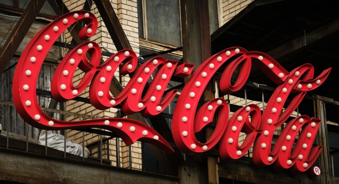 Large 3D sign of the Coca-Cola logo on the side of building.