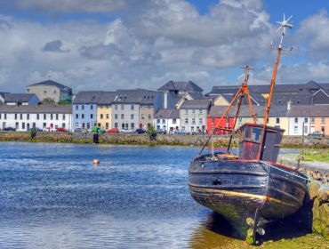 A small rowing boat in the foreground with Galway city in the background with a long row of colourful houses.