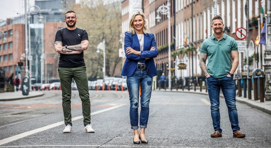 Two men and one woman are standing together on a street in Dublin to mark a new investment in Lucky Beard.