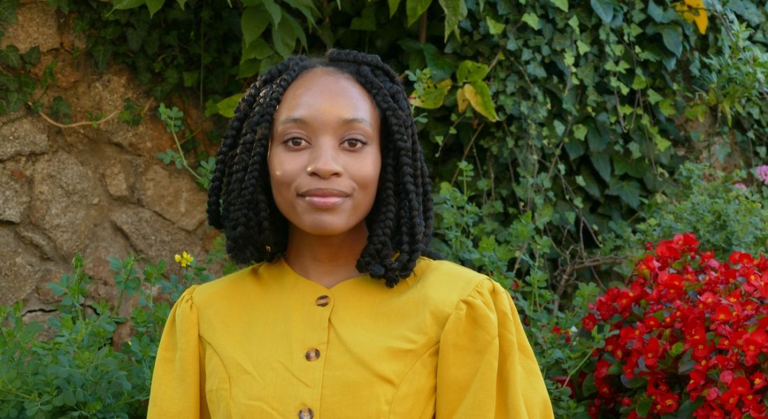 Reabetswe Zwane, who is doing a PhD in computational chemistry, is standing outdoors and smiling into the camera while wearing a bright yellow top.