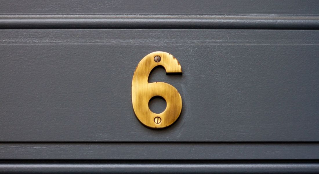 A gold number six on a grey door.
