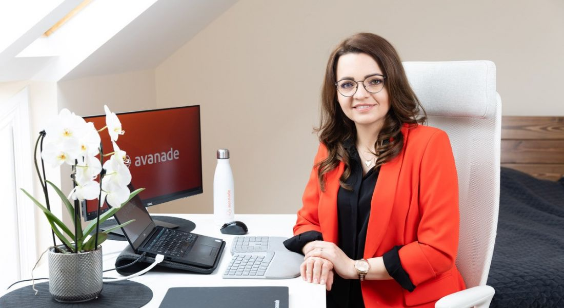 Aga Wiszniewska of Avanade is sitting at her work set-up at home. She is wearing a red blazer and smiling into the camera.