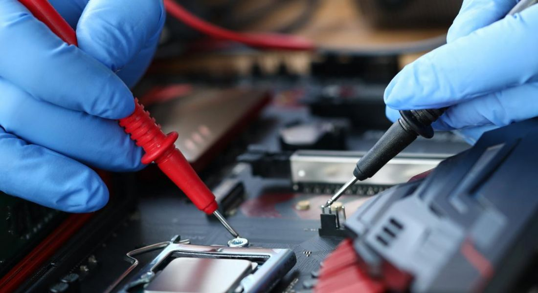 A close up of hands wearing blue protective gloves holding tools, working on an electronic device.
